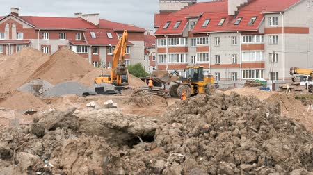 buldozer : MOSCOW, RUSSIA - JULY 07, 2017: Construction vehicles and builders on construction site. The builders work into the large clay pit for the construction of an apartment complex in summer day