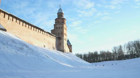 deslizamento : VELIKIY NOVGOROD, RUSSIA - JANUARY 21, 2017: Children sliding down from slides on a sled in winter in the background of the old historical walls of Kremlin of Veliky Novgorod, Russia