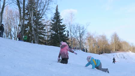 deslizamento : VELIKIY NOVGOROD, RUSSIA - JANUARY 21, 2017: Little children sledding downhill on a sunny winter day