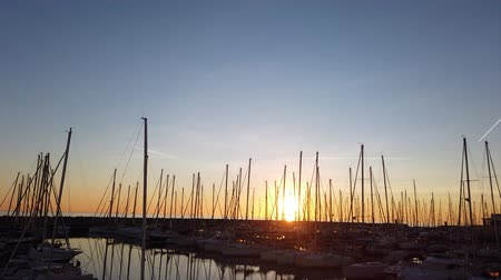 Ostia Lido Rome, Italy - January 15, 2019: Sunset time lapse in golden hour at tourist harbor in Rome, Many sailboats are moored, some planes leave their trails in the sky with seagulls fly around