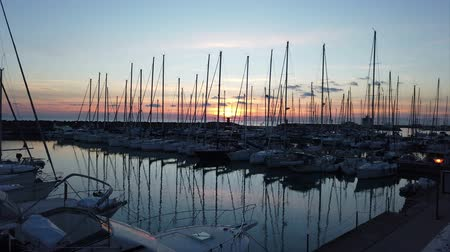 Ostia Lido Rome, Italy - February 03, 2019: Scenic time lapse of the sunset at the marina in Ostia with many sailboats moored by the wind and a suggestive atmosphere