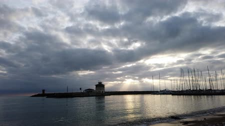 Ostia Lido Rome, Italy - February 08, 2019: Awesome time lapse at the marina in Ostia Lido with dramatic light and beautiful reflections on the sea, the sunbeams filter through a fantastic cloudy sky
