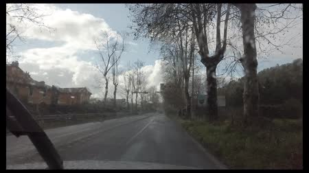 Rome, Italy - February 03, 2019: Real time rain falling on the windshield, running along the road leading to the center of Rome. Wideo