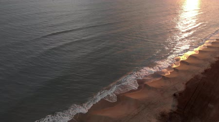 hale : Aerial view of sunset over the sea with waves crashing on the shore with beautiful reflections on the water Stok Video