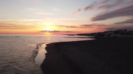 天窓 : Beautiful sunset in the Roman coast at Ostia Lido with calm sea, reflections on the water spectacular sky and a relaxing atmosphere