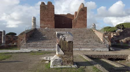 evsahibi : Landscape at Roman archaeological excavations of Ancient Ostia with the Capitolium surrounded by ruins, columns and remains of statues and bas-reliefs