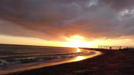 sahil : Beautiful time lapse sunset in the Roman coast at Ostia Lido, the view of the pier and people silhouettes in cloudy sky with beautiful reflections Stok Video