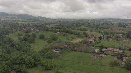 farmhouse : Awesome aerial view of Italy countryside with green valley and hills and forest, farmhouses and cultivated fields Stock Footage