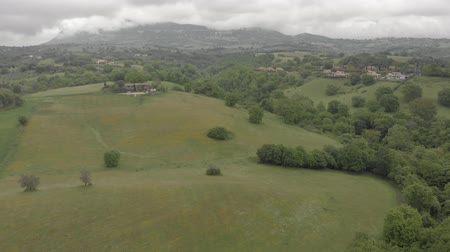 Awesome panoramic aerial view above italy countryside with oak forests and green valley