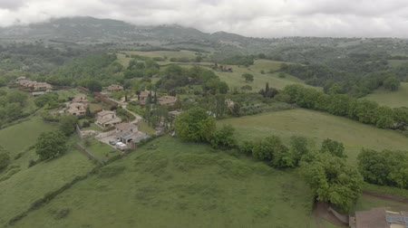 Aerial view - Wandering over countryside and green valleys with woods and hills