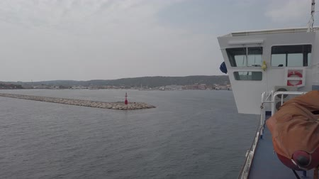 The ferry slips down to the entrance of Saint Peter island harbor with its breakwater and red lighthouse and distance the urban skyline and hills Wideo