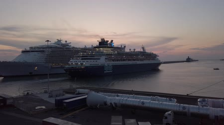 Civitavecchia, Italy - September 19, 2019: Beautiful sunset at Civitavecchia harbor in Rome, with lights reflections in the sea and many seagulls in flight awesome sky, meanwhile in Pullmantur cruise ship, from Royal Caribbean Cruises Ltd fleet of the por