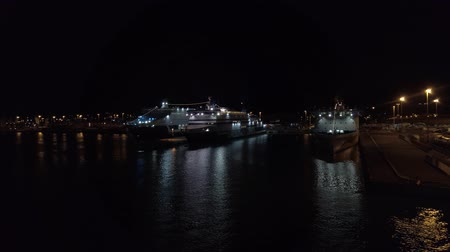 паром : Civitavecchia, Italy - September 19, 2019: Pier with night lights in the port of Civitavecchia in Rome with cruise ships and ferry boats moored on the quay. The ship moving out the port to travel on the sea in a beautiful september night.