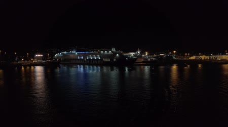 паром : Civitavecchia, Italy - September 19, 2019: Looking at the port of Civitavecchia in Rome with cruise ships and moored on the quay. The ship moving out the port to travel on the sea in a beautiful september night.