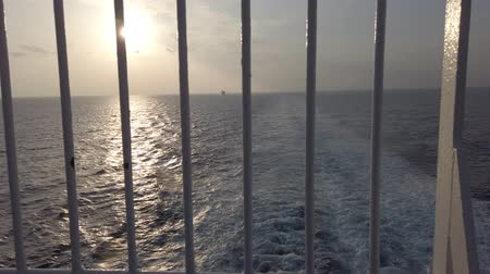 Watching the sunset over the ocean and reflections on the sea between steel bars and hoping for change - First-person 4K shoot Wideo