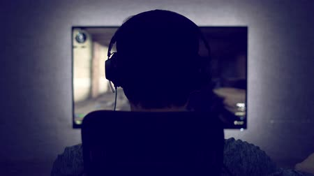 masaüstü : Gamer from back in headphones sits in front of a monitor with video game in dark room Stok Video