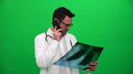 Doctor Holding X Ray Results And Talking On The Phone On A Green Screen