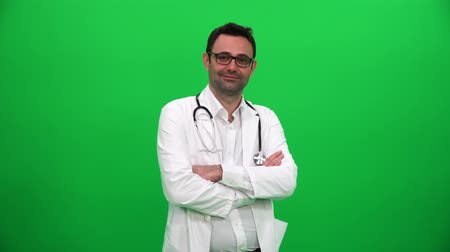 Doctor Turning and Looking at Camera on Green Box Background Vídeos