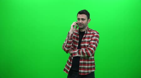 Young Man Talking on the Phone Against a Green Screen