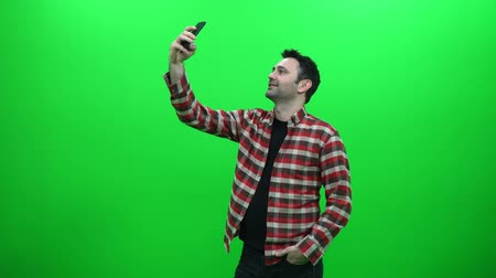 Man Taking A Selfie Photo With His Smartphone On A Green Screen