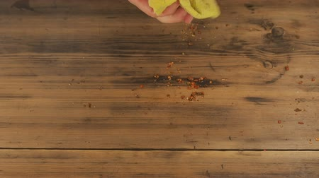 wipe off : The man wipes the table of the old, brown boards, yellow cloth. Mans hand removes the remnants of the spices off the table, removes debris. The view from the top. Stock Footage