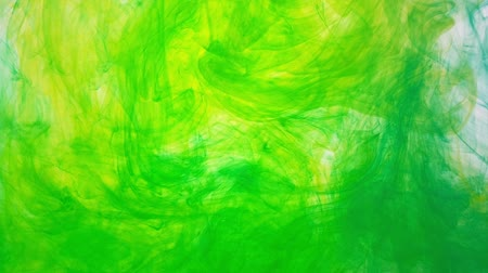 yellow ink : Paint movement in water. Colored droplets are mixed and dissolved. Drops of color ink swirling in a water. Abstract background of acrylic color ink swirling in water.