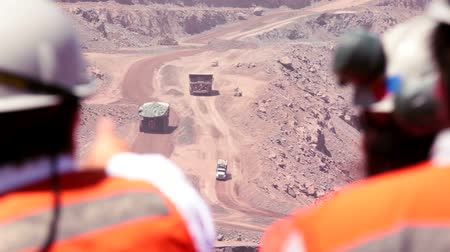 Workers watch activity in a copper mine