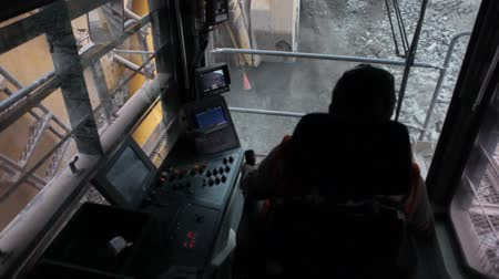 Inside view of an excavator scoops up a huge bucket of dirt and ore and is About to empty it into the rear tray of the haulage truck.