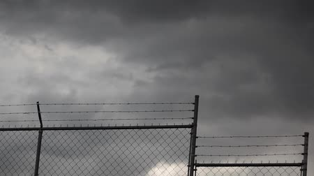 farpado : Stormy Clouds and Fence. barbed wire Stock Footage