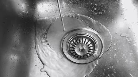floş : Close up view from above of water pouring into a stainless steel sink