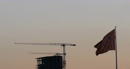isztambul : Turkish flag waving front of construction  building at sunset Stock mozgókép