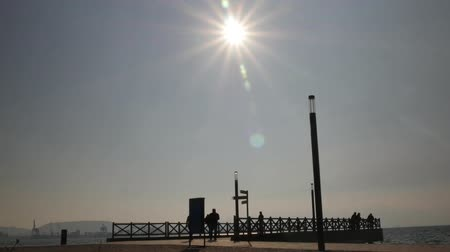 refletir : Sea Pier Silhouette Against Sun. Time Lapse
