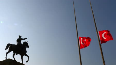 flag half mast : Ataturk riding horse sculpture silhouette and half-staff Turkish flag. Stock Footage