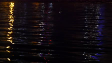 blue color : Close-up of reflection of city illumination on sea surface in darkness. Stock Footage