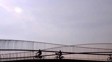 sight seeing : Silhouette of riding bicycle people over the bridge against the blue sky.
