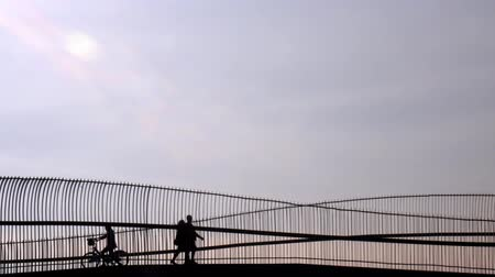 sight seeing : Silhouette of riding bicycle woman and couple walking over the bridge. Stock Footage
