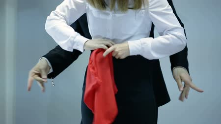 persuasion : magician shows trick with red scarf and woman on dark background
