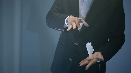 persuasion : magician shows trick with flying white napkin on black background. Stock Footage