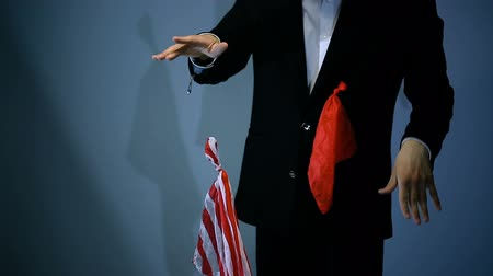 inducement : magician shows trick with flying red napkin on black background.