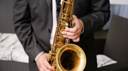 caz : Saxophonist in a black suit playing on golden saxophone. Jazz music.