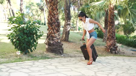 kostka : young brunette woman in shorts, sunglasses and heels comes with suitcase and twisted ankle his leg between trees
