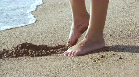 resting : tanned female legs on beach. water splashing on feet in ocean on sandy beach