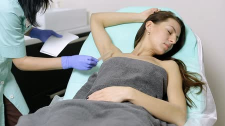 mezoterapia : cosmetologist applies gel to armpits of patient before epilation procedure