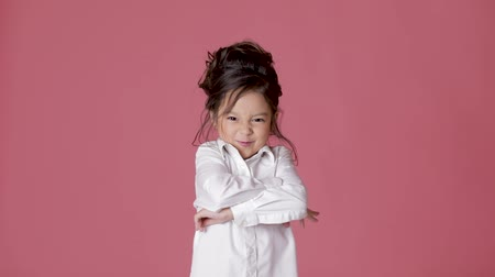přestupek : cute little child girl in white shirt shows different emotions on pink background.