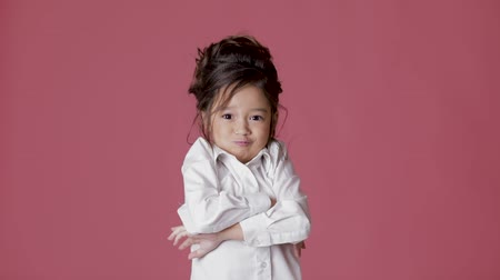удивительный : cute little child girl in white shirt shows different emotions on pink background.