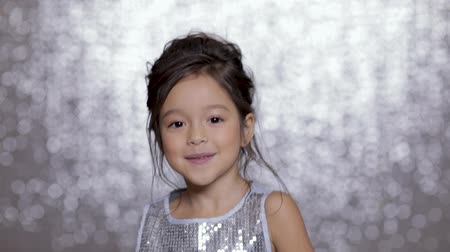 festa : beautiful smiling little child girl in a silver dress dancing on background of silver bokeh.