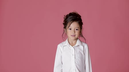 приехать : cute little child girl in white shirt shows different emotions on pink background.