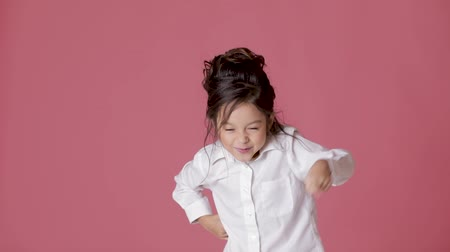 take offense : cute little child girl in white shirt shows different emotions on pink background.