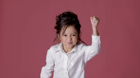kom : cute little child girl in white shirt shows different emotions on pink background.