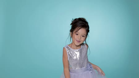 幼稚な : beautiful little child girl in silver dress dancing on blue background. 動画素材